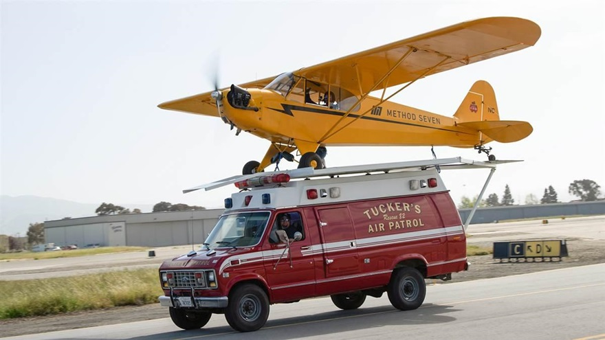 Justin Ramsier drives a 1990 ambulance while Eric Tucker pilots his J-3 Cub from a platform attached to the ambulance roof.