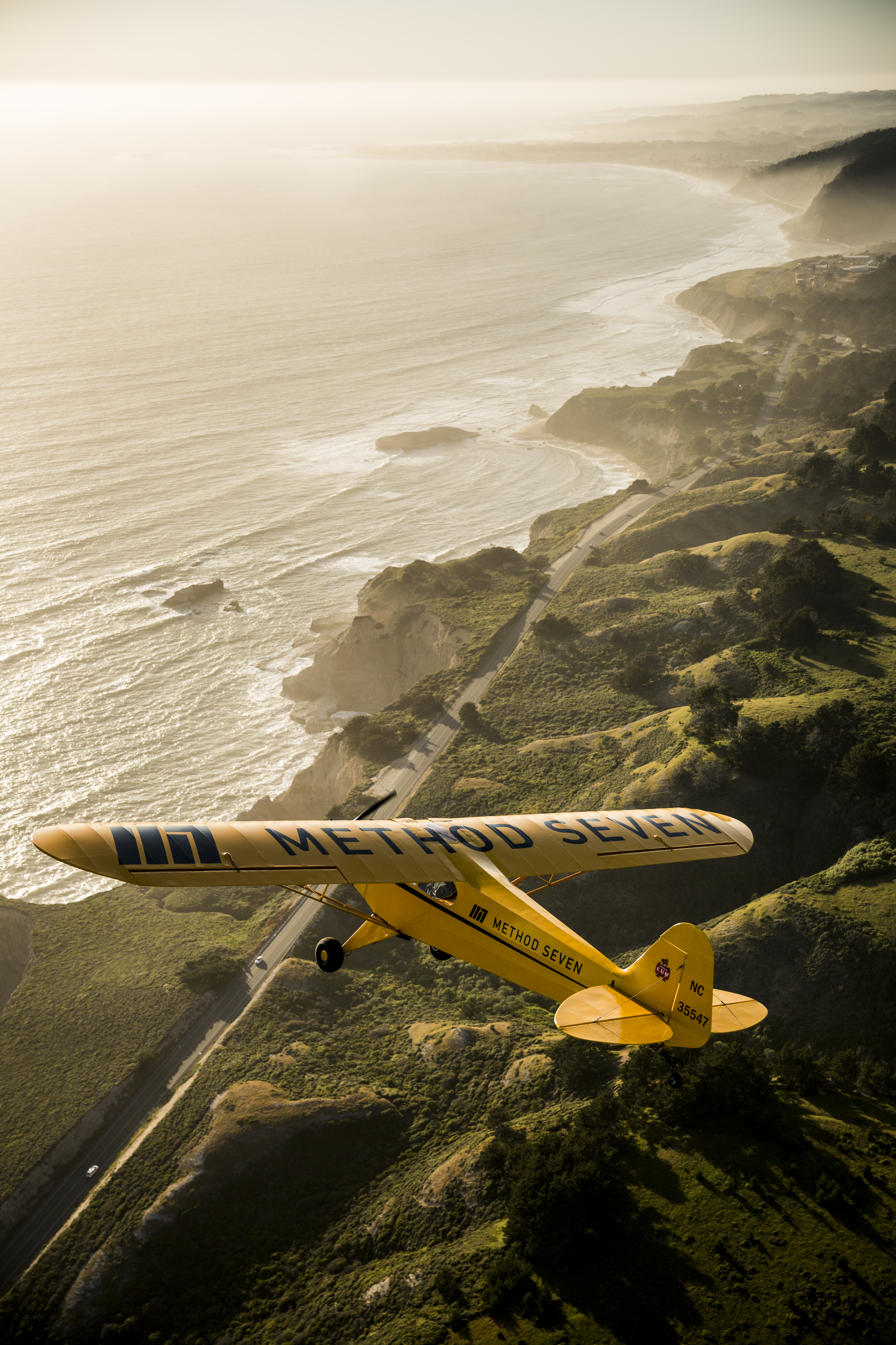 Eric Tucker flying his J3 Piper Cub over Highway 1 in California