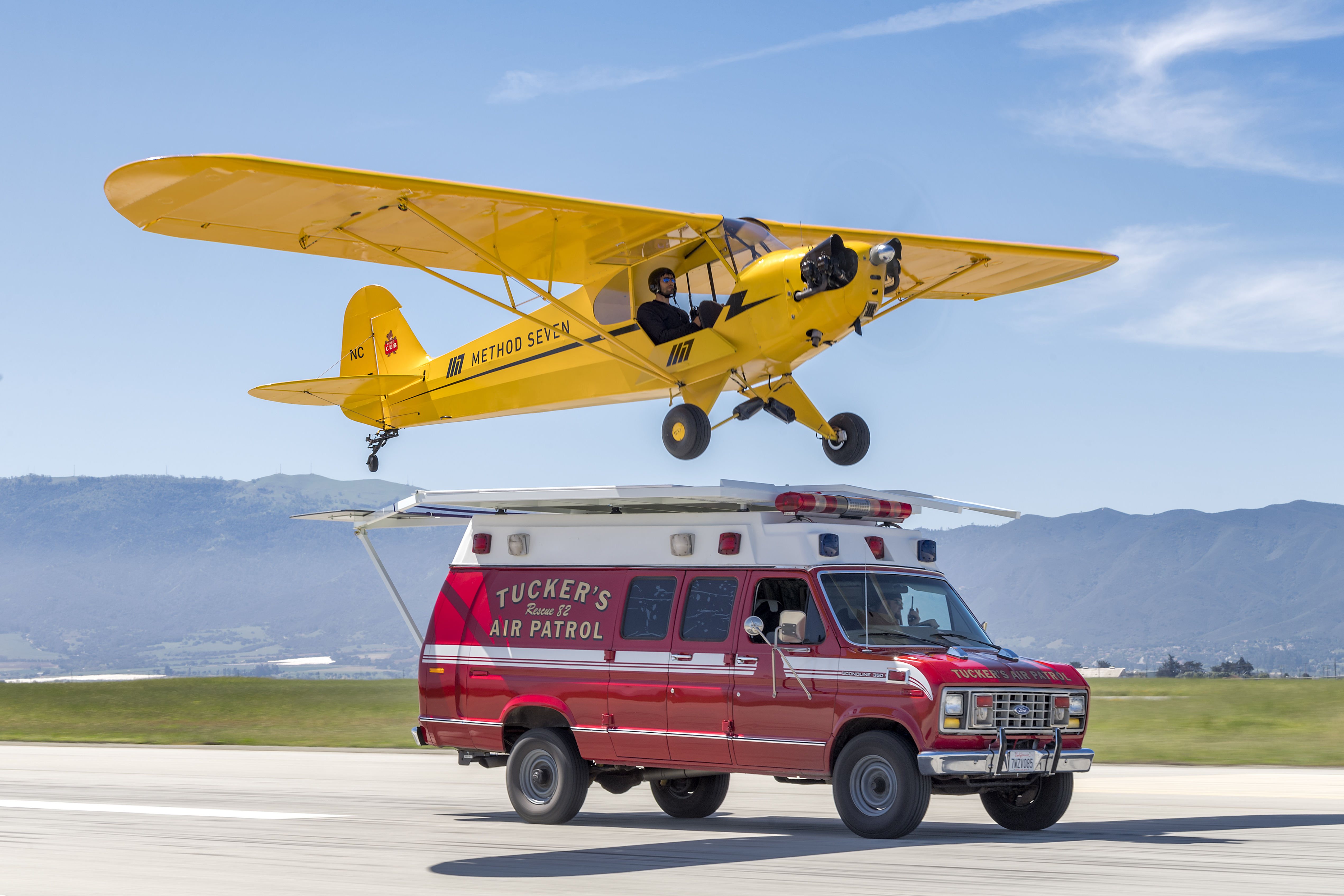 Photo of Eric Tucker practicing his stick and rudder skills as he flies low over the ambulance in his J3 Piper Cub.